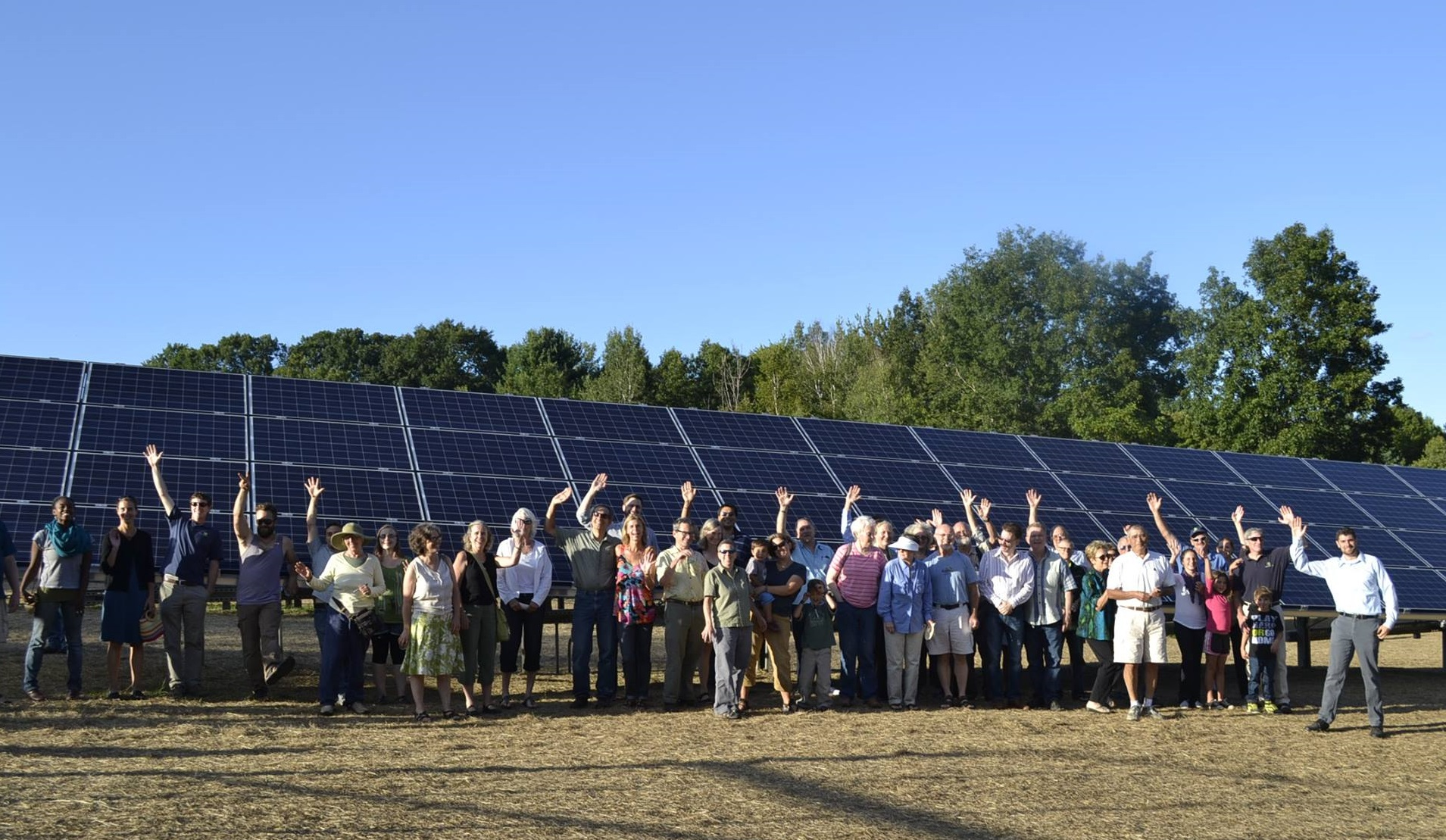 Group of people in front of solar panels